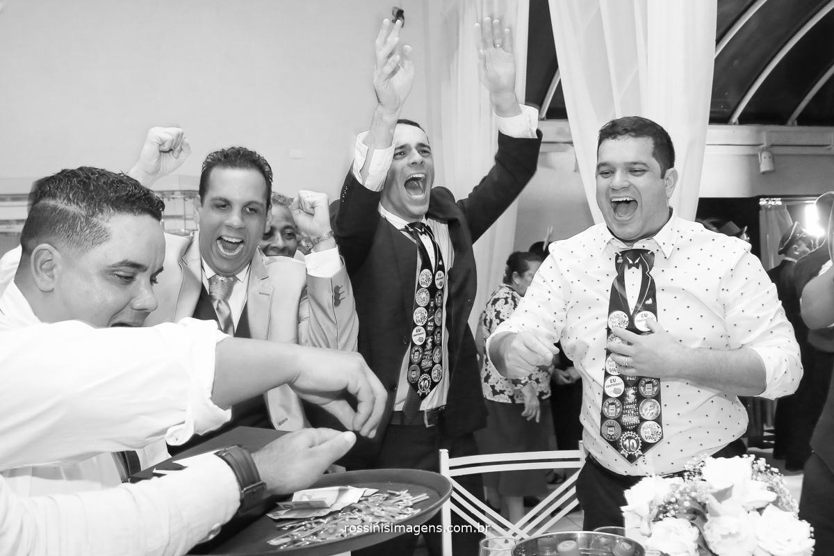 fotografia de casamento noivo passando a gravata muito animado