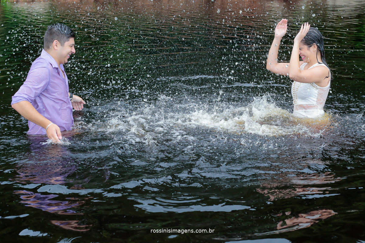 foto de casal brincando na agua do lago na praia felizes e muito animados, fotografia fantástica de ensaio pre wedding, pre casamento, ensaio, trash the dress