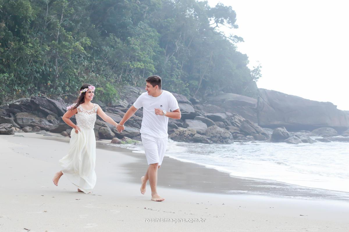 imagem de fotografia de casal correndo na beira da praia felizes, apaixonados e envolvidos com o clima do casamento