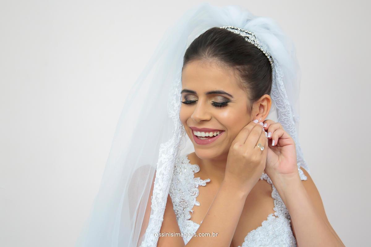 noiva julianne colocando o maravilhoso brinco para o casamento, dia incrível inspiração de casamento