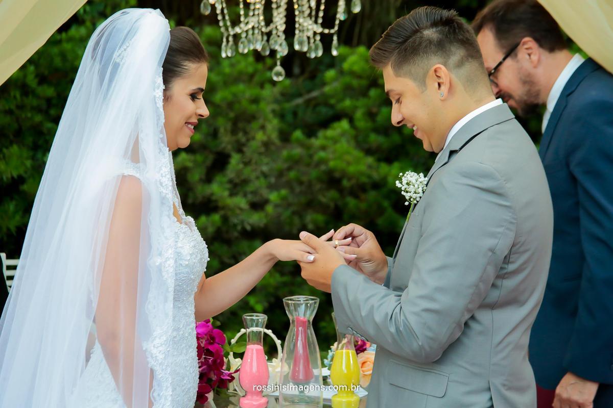 noivo colocando a aliança em sua noiva, simbolo que sera eterno e para sempre