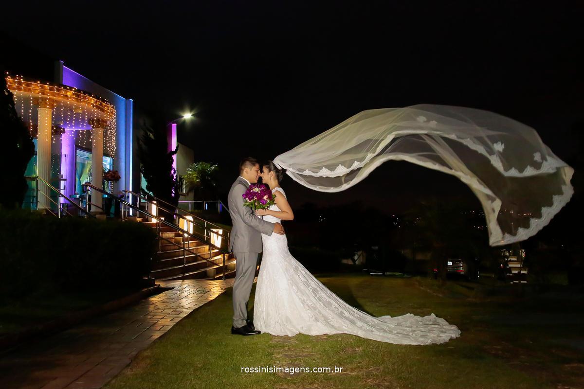 fotografia de casamento noivos abraçados e o veu da noiva voando, foto inspiração de noiva, foto criativa, casamento no campo