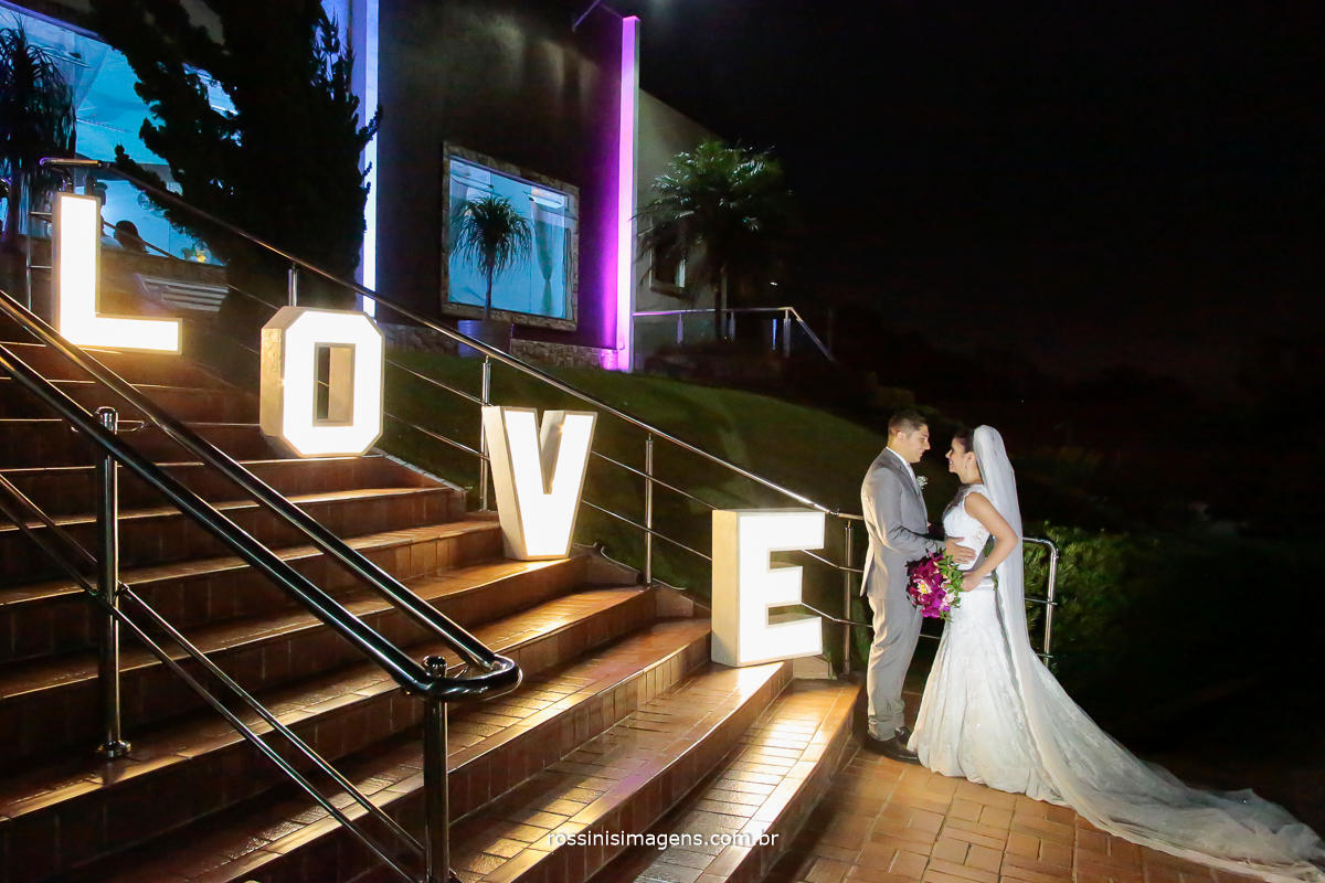 casamento no campo, casamento em poá, casal se olhando no fundo dos olhos ao lado a palavra love como decoração, love decorativo para casamento