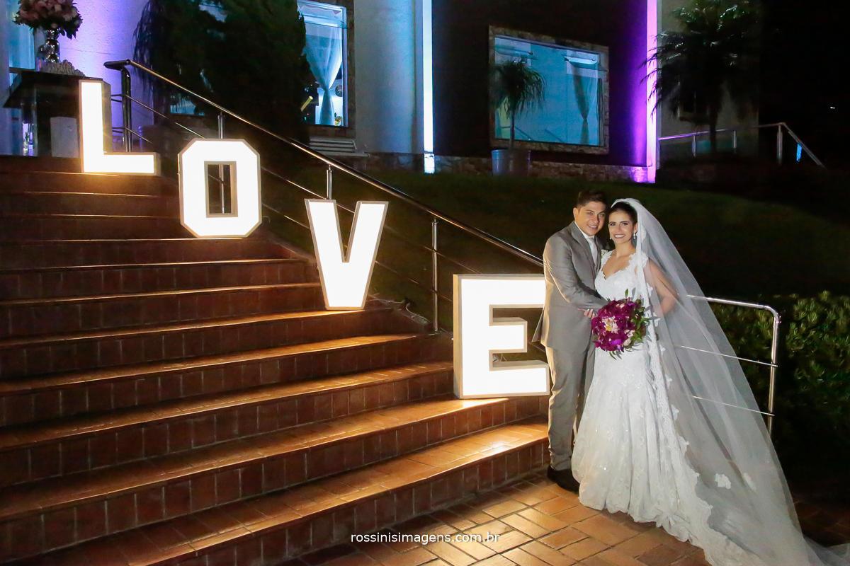 love para casamento caprichos buffet, marido e mulher abraçados ao lado do letreio