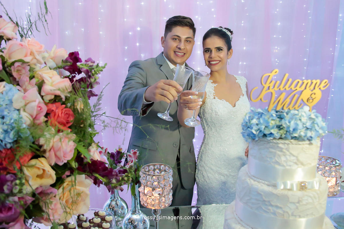 fotografia de casamento noivos no bolo, noivos brindando, noivos comemorando