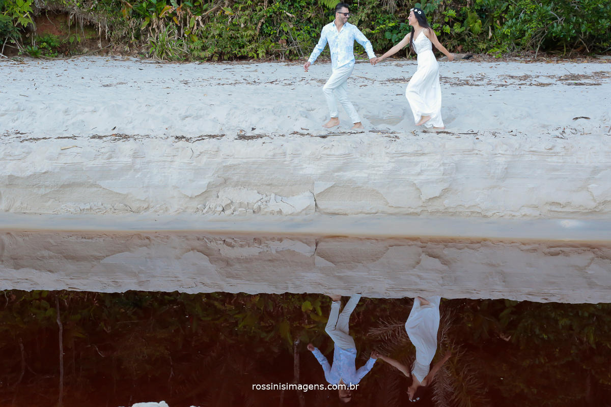 reflexo de casal na praia em dia lindo de sol, casal correndo
