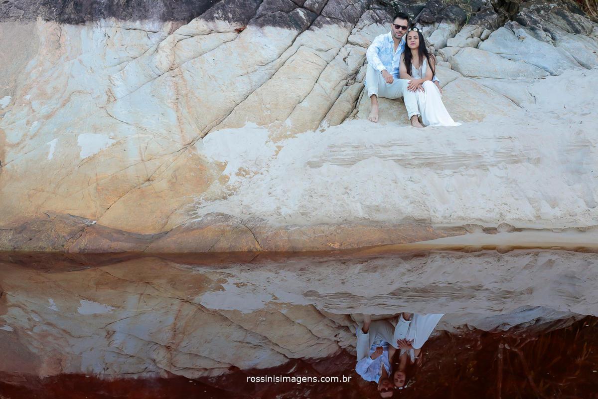 casal sentado na pedra na praia e com reflexo na agua