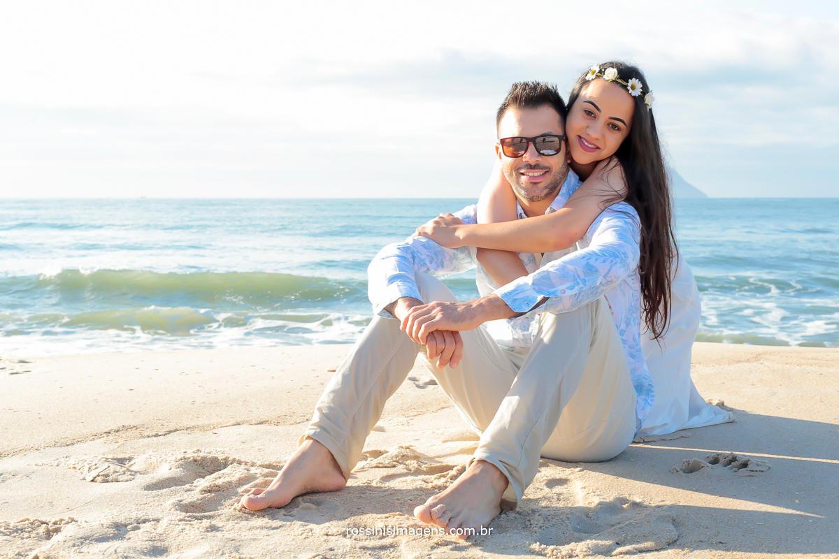 noiva abraçado no noivo sentado na areai da praia em um lindo dia de sol na praia do litoral norte de são paulo