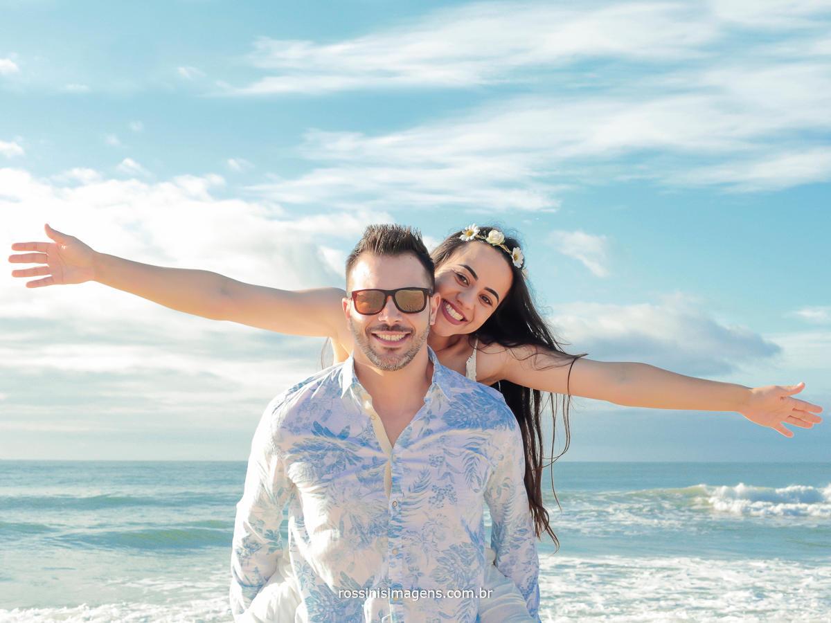 sessão de fotos de casal no ensaio antes do casamento, realizado na praia em um lindo dia de sol com céu azul e mar de águas claras lugares paradisíacos, A melhor empresa de fotografia e Vídeo da região