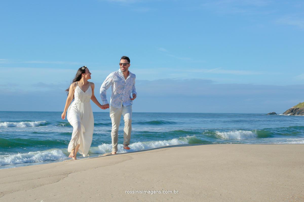 fotografia de casal correndo na praia na sessão de fotos para o casamento, realizado por rossinis imagens