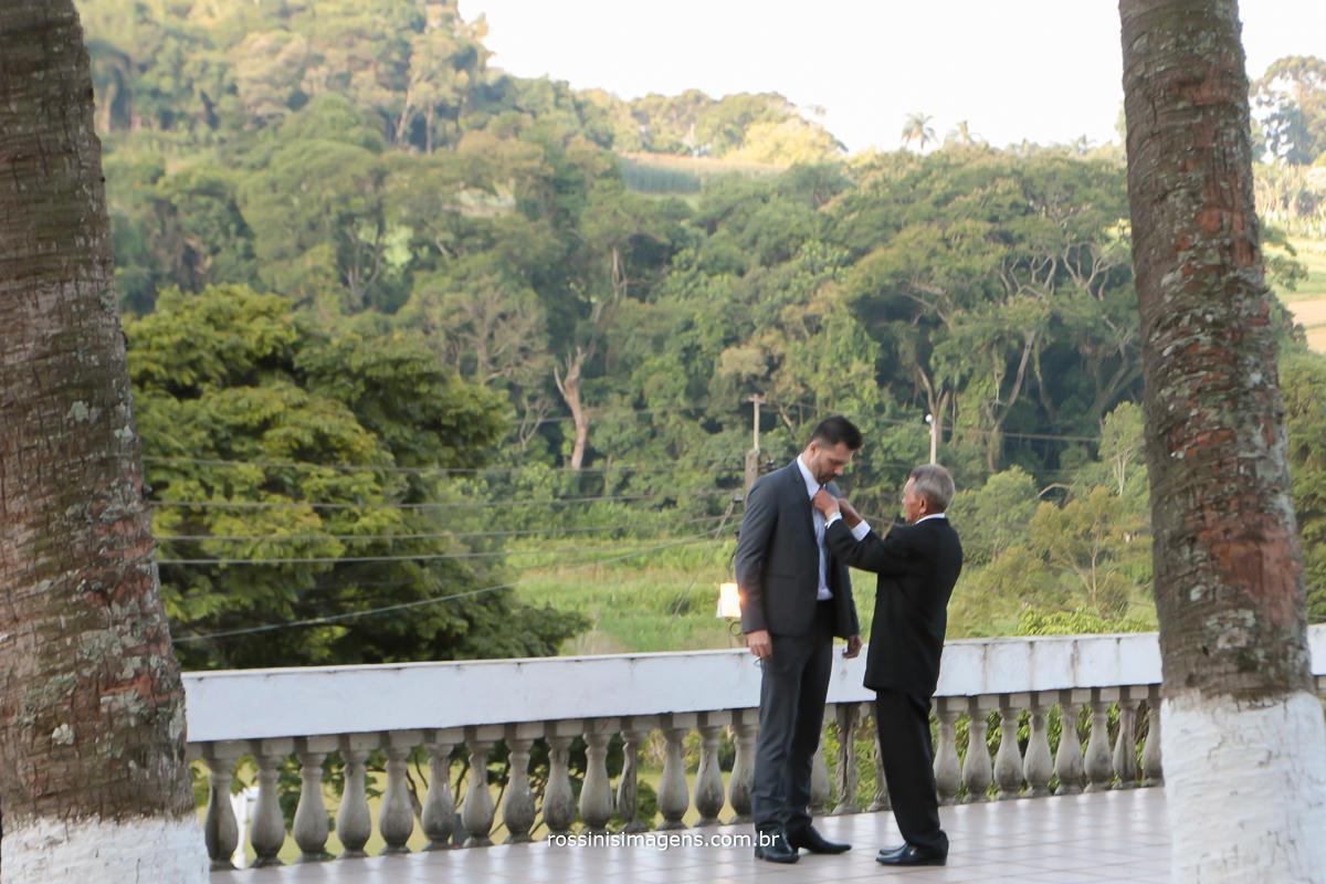 imagem do pai colocando o terno no seu filho o noivo antes da cerimonia de casamento muita alegria