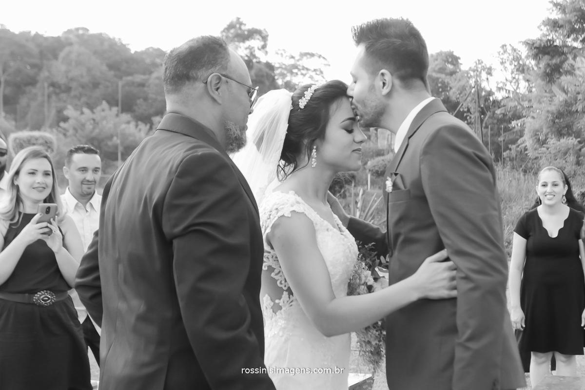 pai entregando sua filha para o noivo no altar, que recebe sua noiva com um lindo e romântico beijo na testa