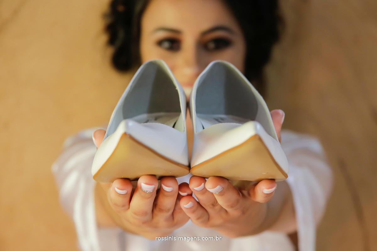 fotografia de casamento, rossinis imagens casamento estudio fotografico em suzano, noiva com o sapato e um lindo sorriso no rosto que transborda de felicidade