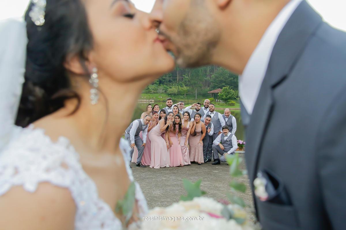 noivos dando um beijo e os padrinhos   aparecendo ao fundo entre os noivos, fotografia de casamento em Suzano na chácara Gyotoku um lindo espaço para cerimonia e recepção e festa de casamento,
