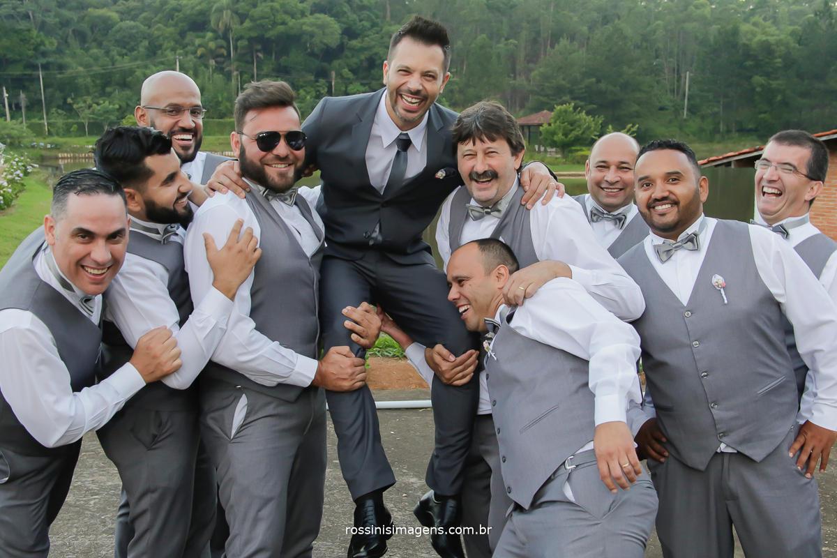 padrinhos pegando o noivo no colo, padrinhos de casamento jogando o noivo para o alto,  fotografia do noivo com os padrinhos apos a cerimonia