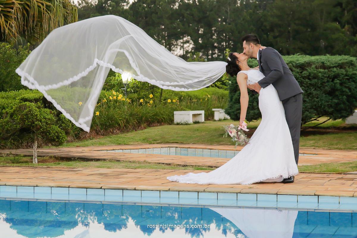 noivo beijando a noiva e o véu voando, véu caindo, fotografia de casamento Natali e Eduardo