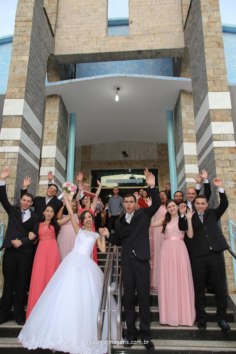 porta da igreja com os noivos e todos os padrinhos, muito animados e vibrantes com essa conquista, foto coletiva,