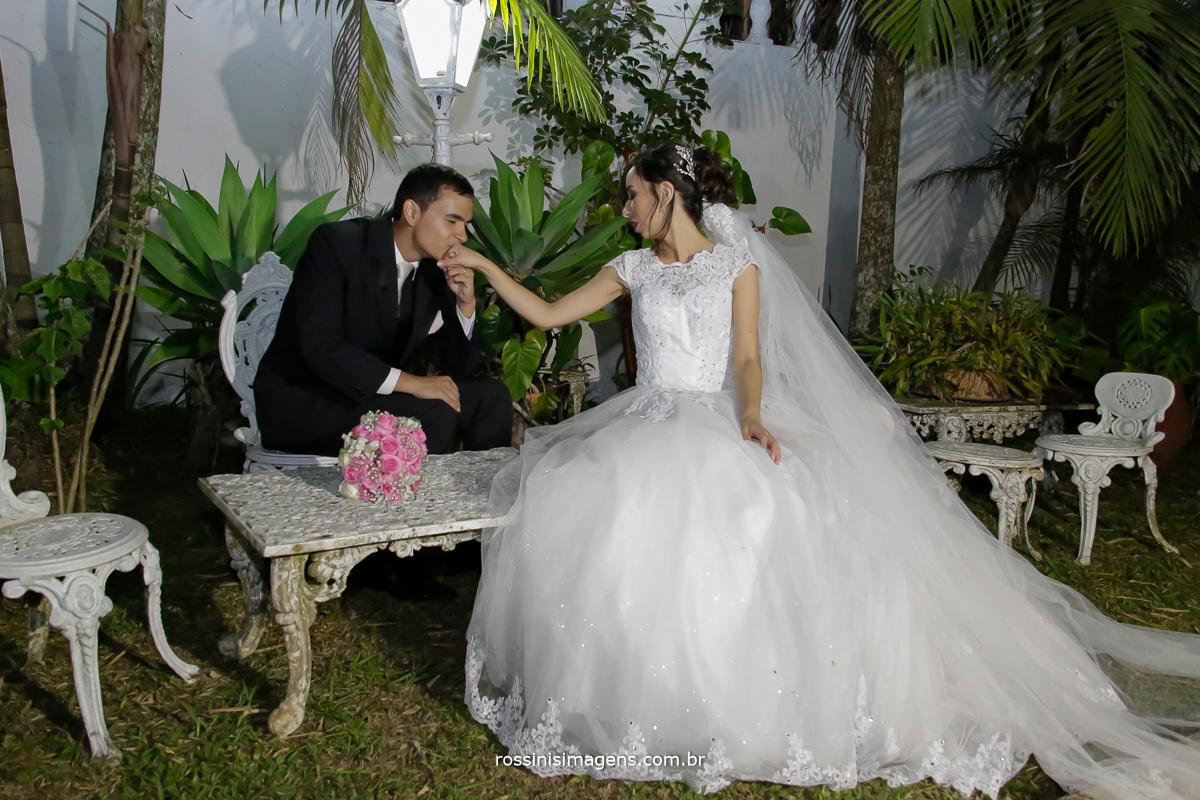 fotografia de casamento, noivos sentados o noivo matheus beijando a mão da noiva Jaqueline