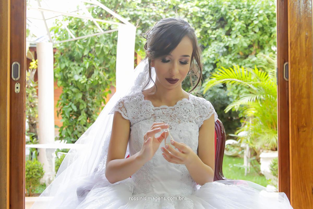 imagem da noiva passando perfume sentada na sala do espço rosina freitas, fotografo de casamento em mogi das cruzes, rossinis imagens wedding day
