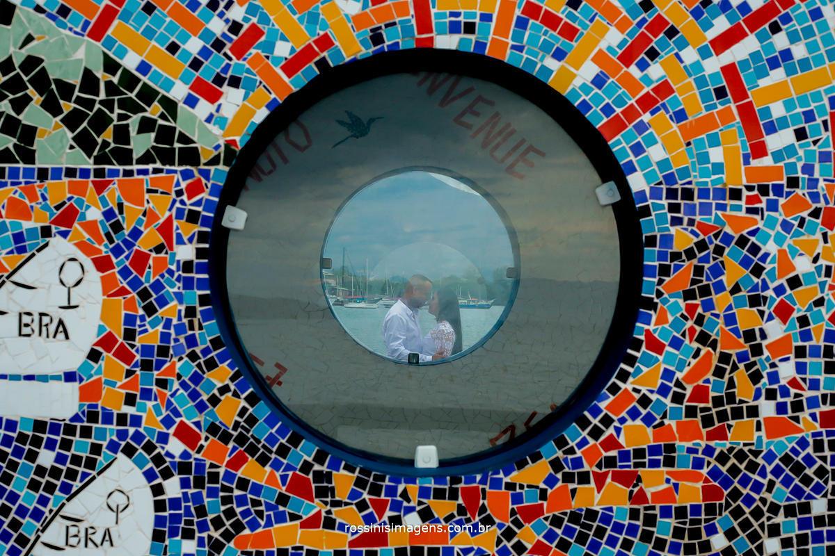 foto de casal através dos vidros circulares do pier em Ilhabela