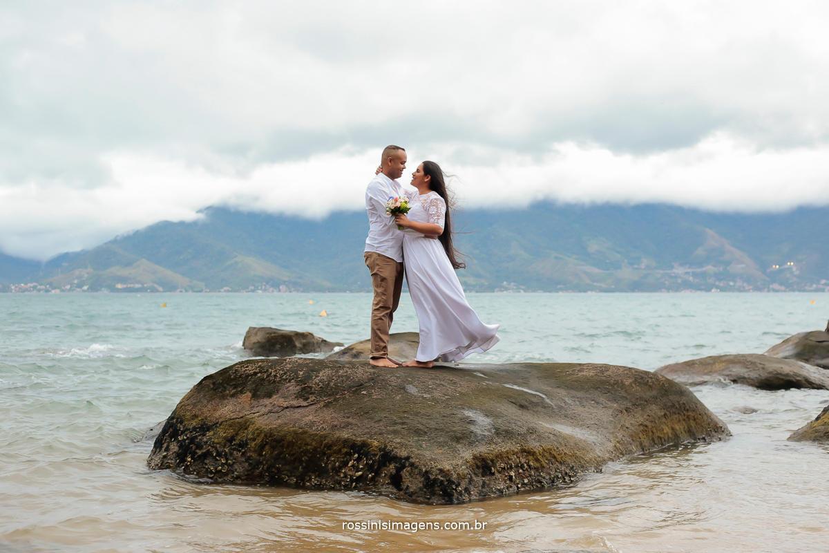casal encima da pedra na praia de ilhabela, lugar ideal para ensaio pre casamento, pos-casamento, casamento, wedding