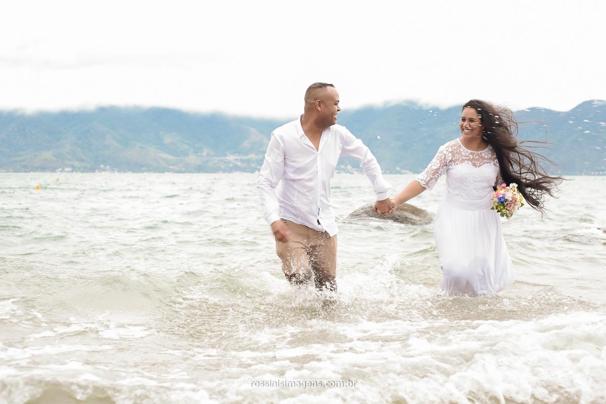 casal correndo dendro da agua na praia de ilhabela