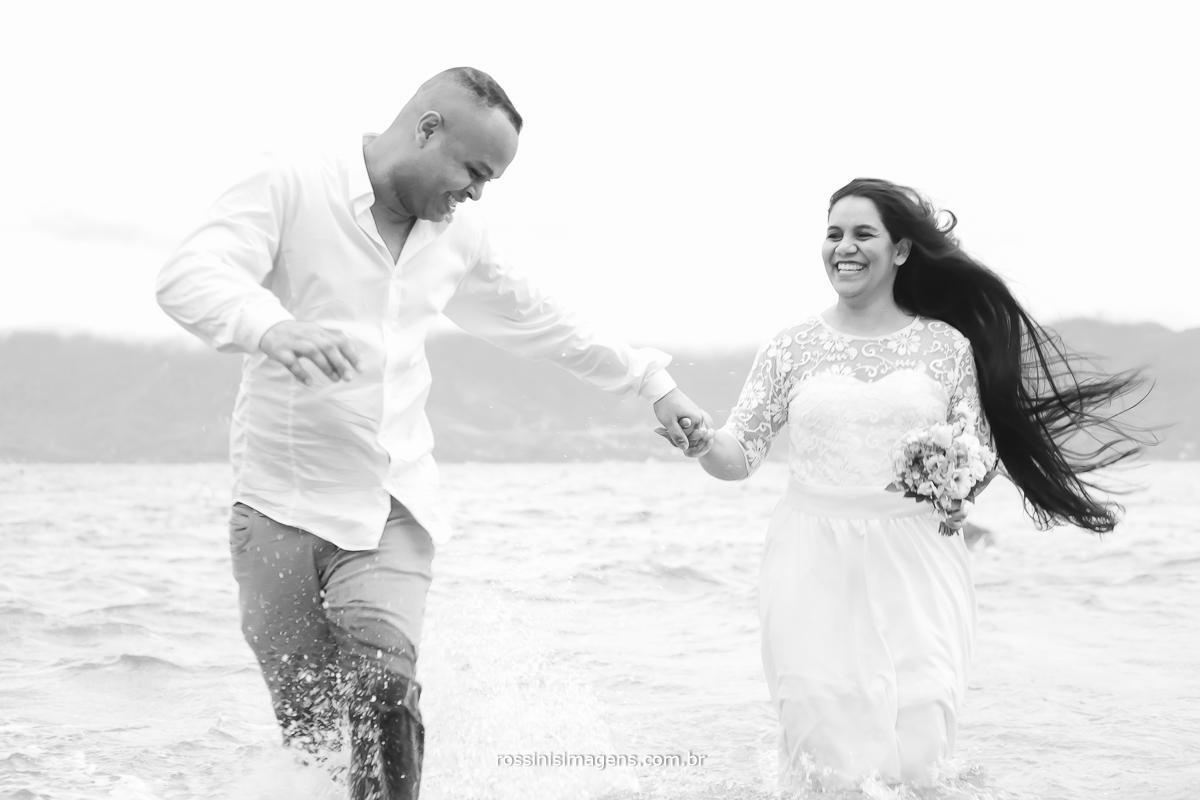 noivo correndo na água e trazendo a noiva correndo feliz, a verdade do casal, ensaio na praia de são paulo