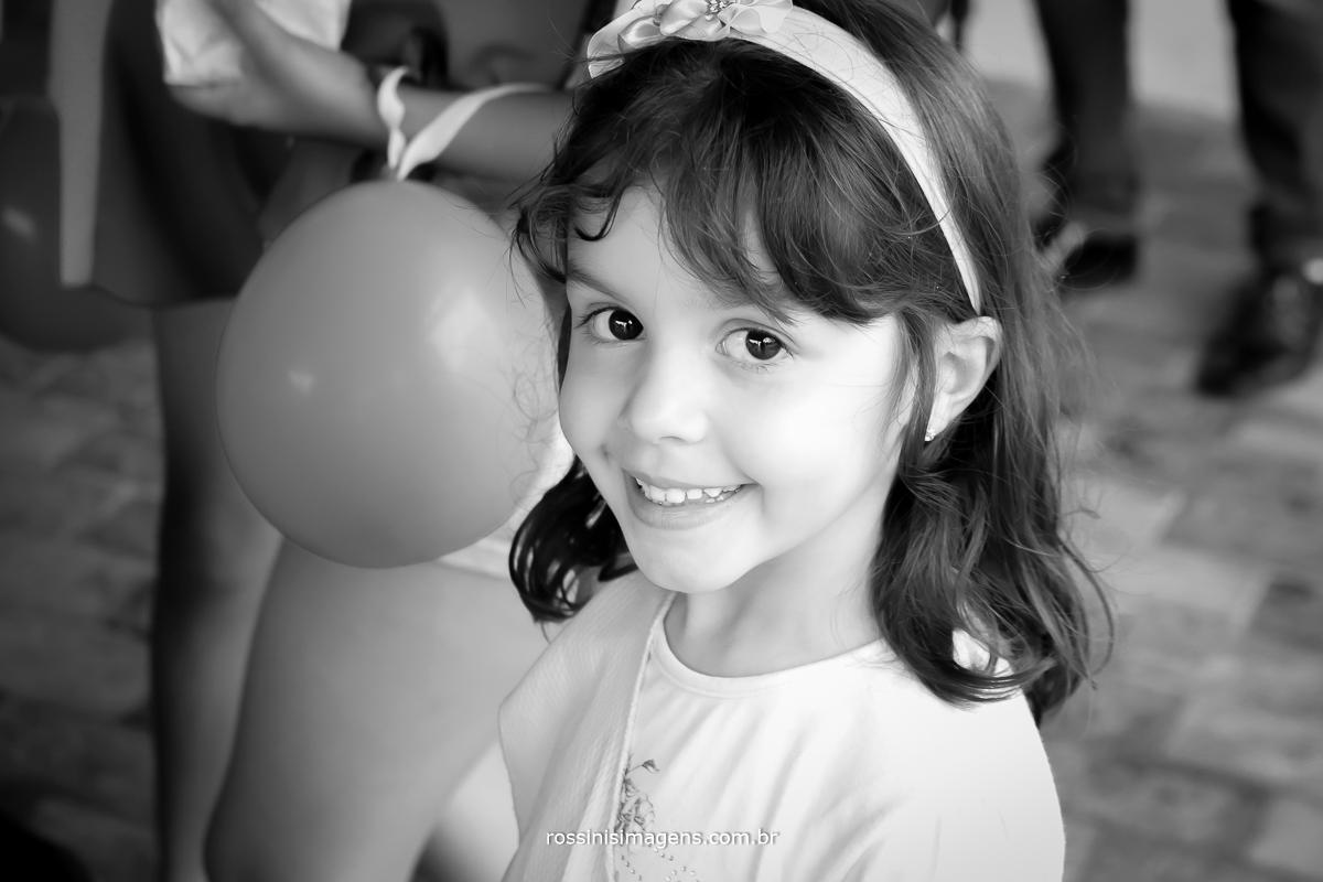 fotografia de aniversario infantil de 5 anos menina olhando para a foto sorrindo e brincando