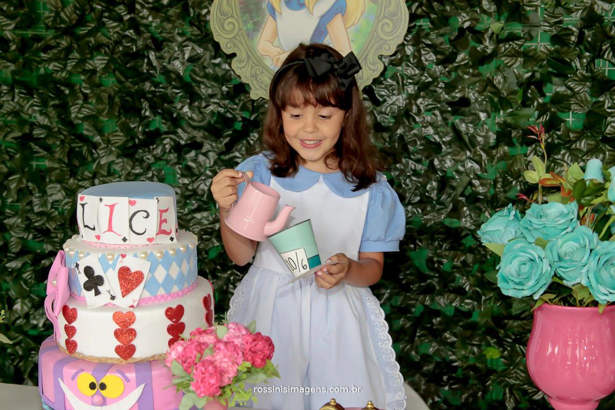 imagem da fotografia da nathalia 5 anos brincando na mesa do bolo com a decoração de alice no pais das maravilhas