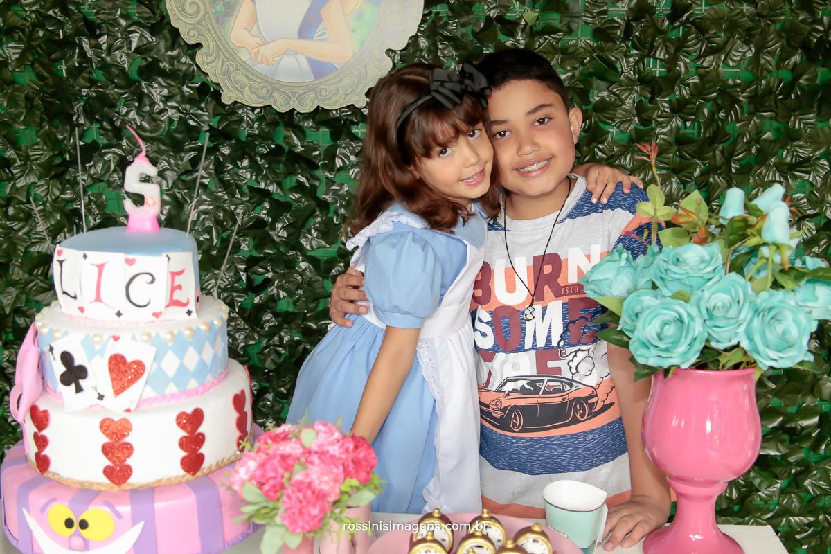 hora do parabéns, nathalia e seu irmão matheus na mesa do bolo abraçados, festa de aniversario de 5 anos