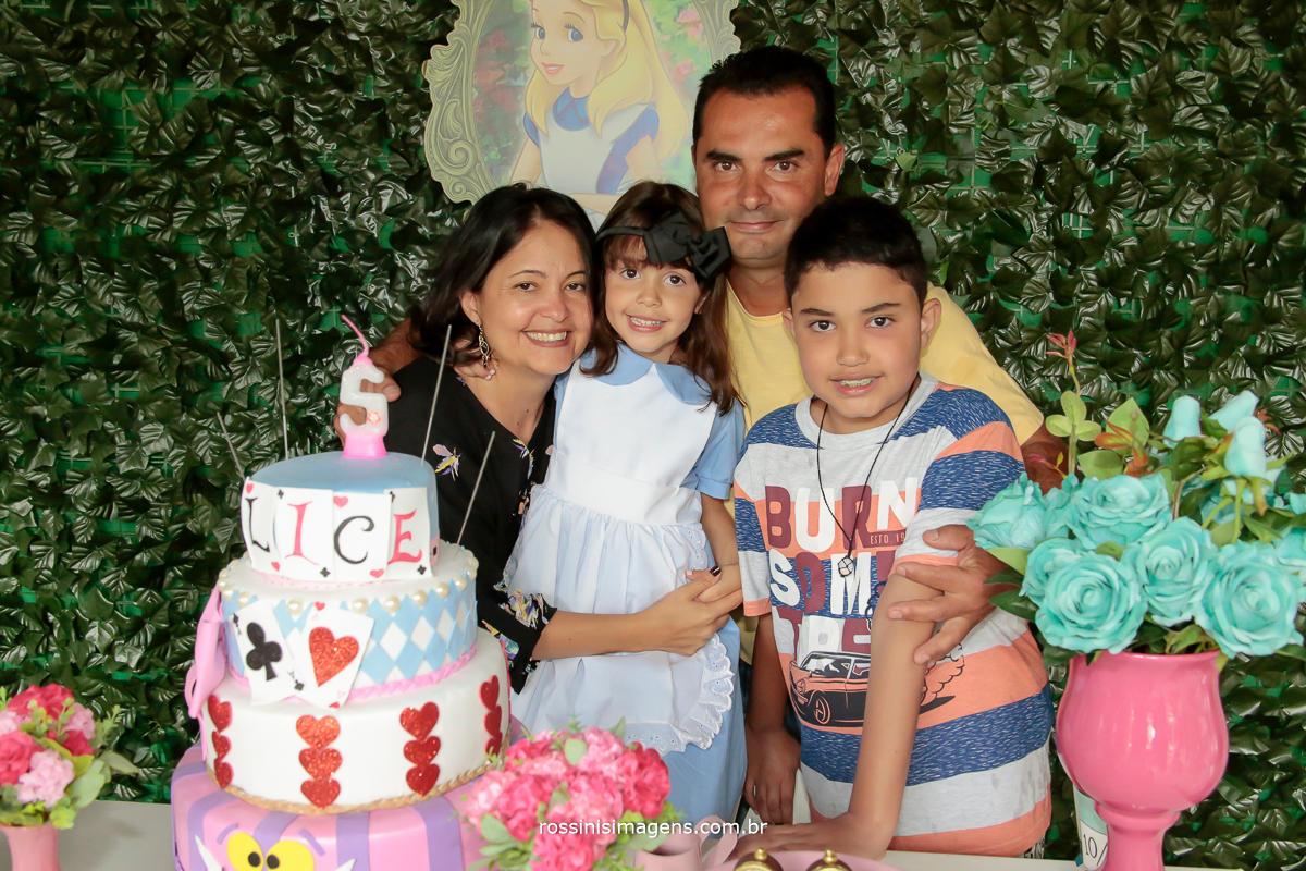 fotografia da familia na mesa do bolo mamãe, papai, irmão e a nathalia, mesa do bolo decorado de alice no pais das maravilhas, aniversario de 5 anos, ideia, temas, dicas, inspirações