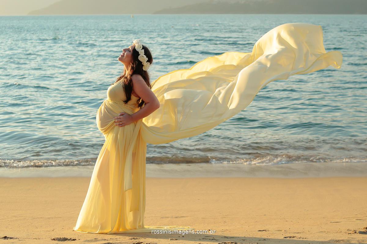 foto de praia com a gestante e vestido voando,