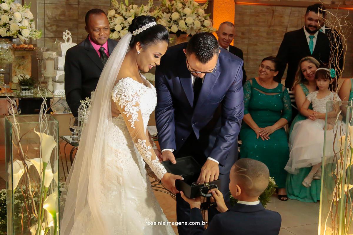 fotografia do pajem entregando as alianças para os noivos
