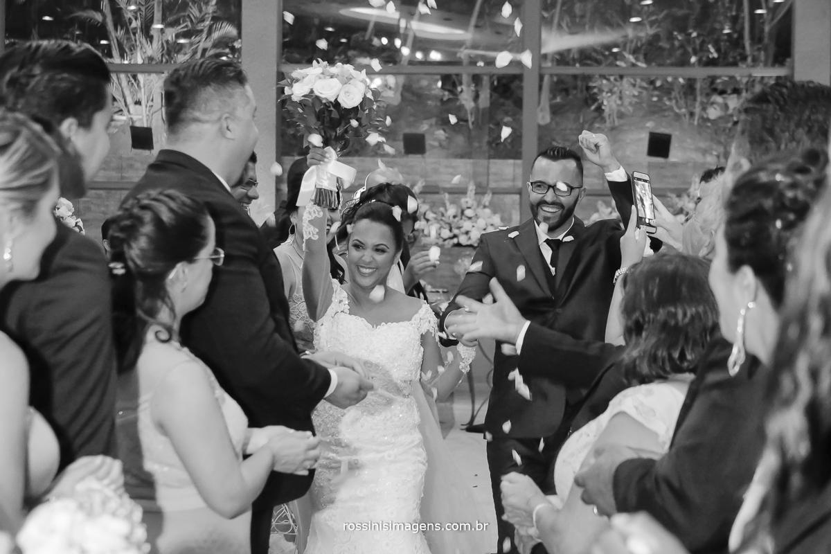 fotografia de casamento saída dos noivos muito animados com chuva de pétalas de flores, rossinis imagens fotografia e video