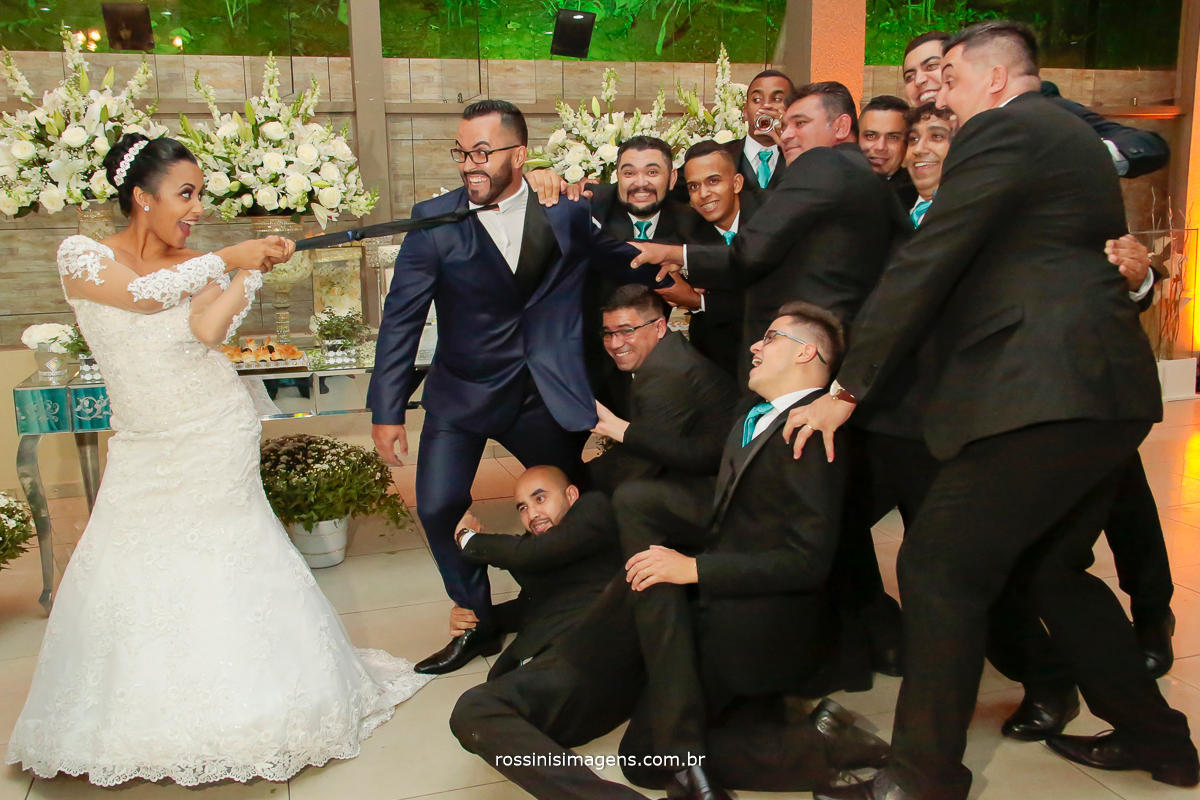 rossinis imagens noiva puxando noivo pela gravata e os padrinhos segurando o noivo