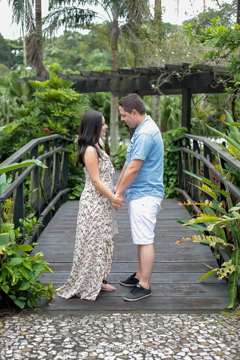 casal no ensaio pre casamento na ponte no centro de riviera de sao lorenço de maos dadas com o olhar apaixonado