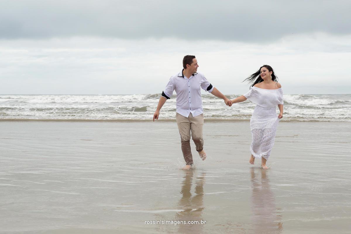 pre wedding, pre casamento jefferson e franciele correndo na praia, felizes e contentes, noiva de branco, noivo de roupa clara, combinando com a noiva