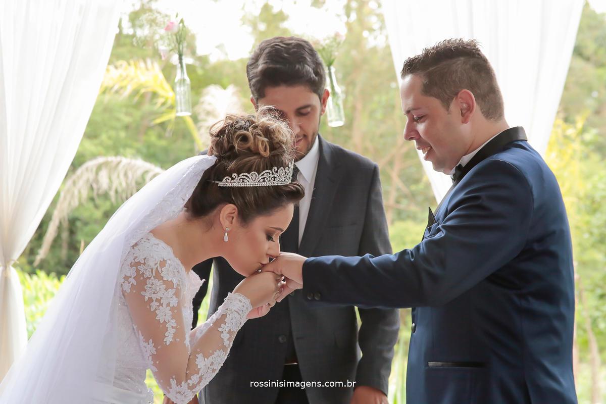 fotografia da noiva beijando a aliança do noivo na cerimonia de casamento na chacara em suzano, rossinis imagens fotografia e video de casamento melhor preço e qualidade da região, grande abc, rio grande da serra, mogi das cruzes, guarulhos, tatuapé