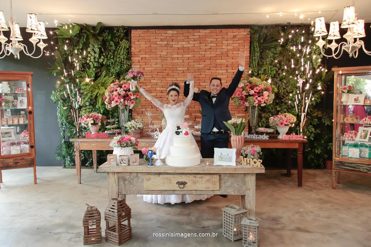 fotografia de casamento noivos na mesa do bolo, com chuva de prata do DJ Royal som e iluminação cênica a melhor da região