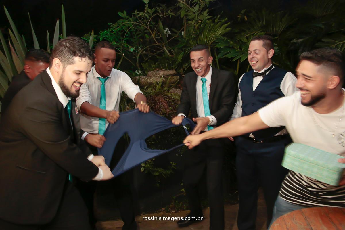 fotografia de casamento gravata do noivo que rendeu a cueca inteira para os amigos, padrinhos rasgando a cueca do noivo, fotografia diferente noivos que fazem a diferença no casamenot