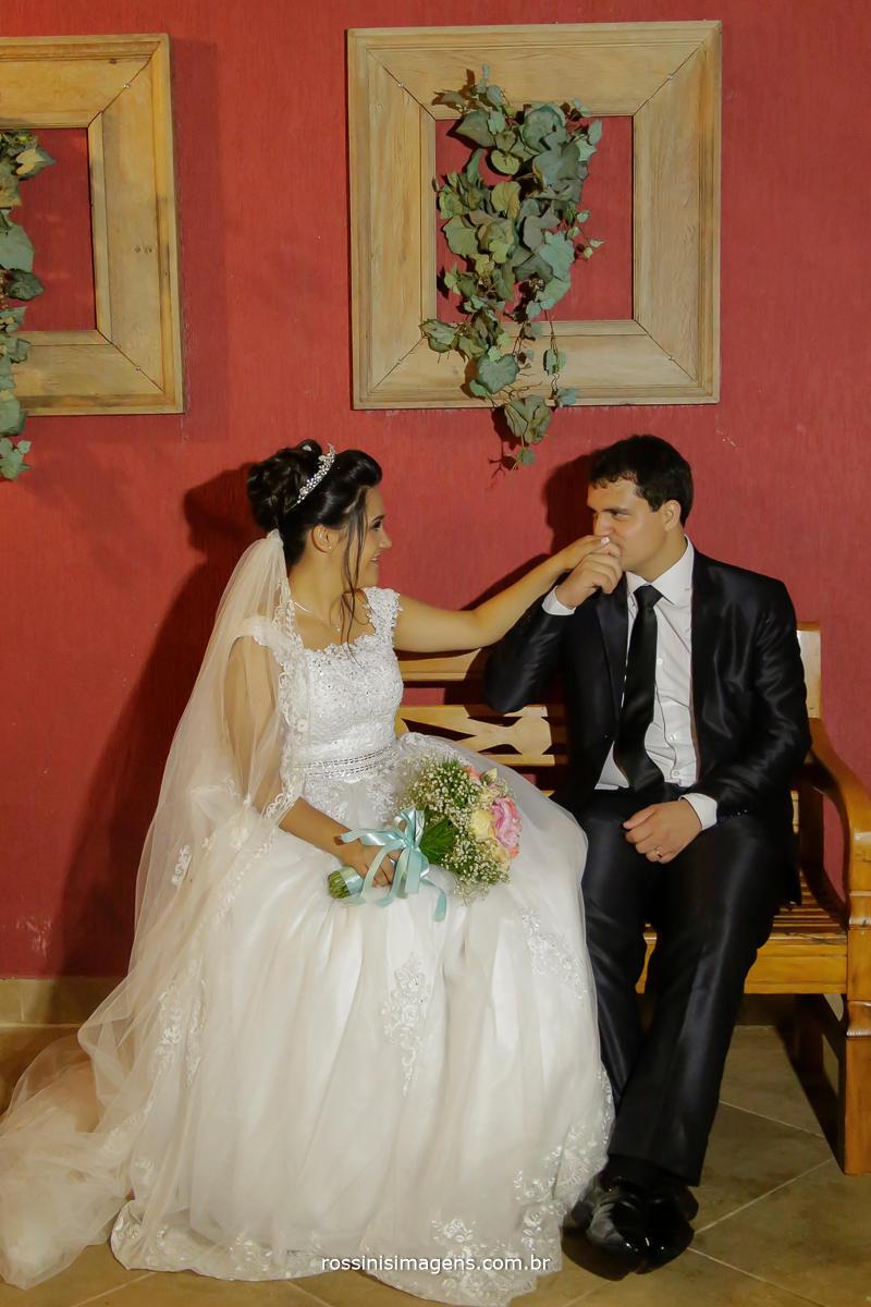 rossinis imagens fotografia de casal de noivos sentados em um banco de madeira e o noivo apreciando a beleza de sua esposa