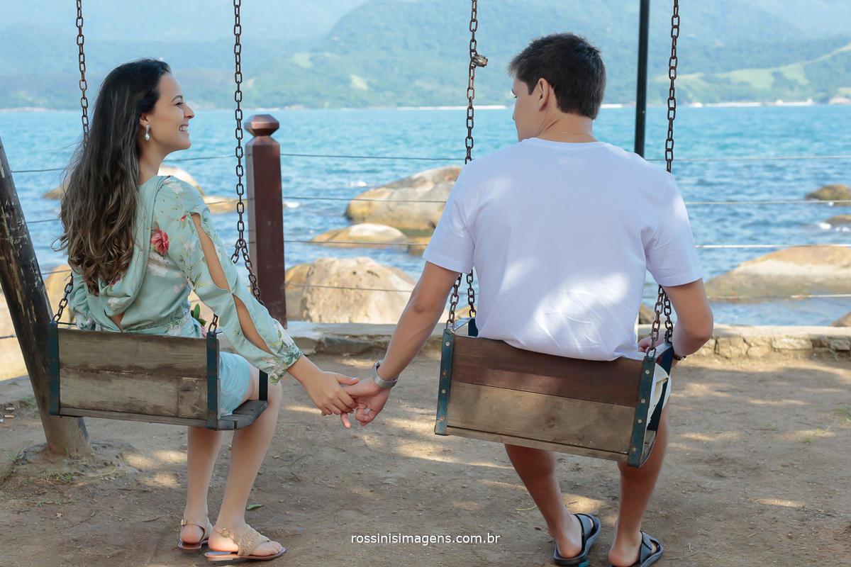 fotografia de casal sentado em balança de mãos dadas e olhando um para o outro