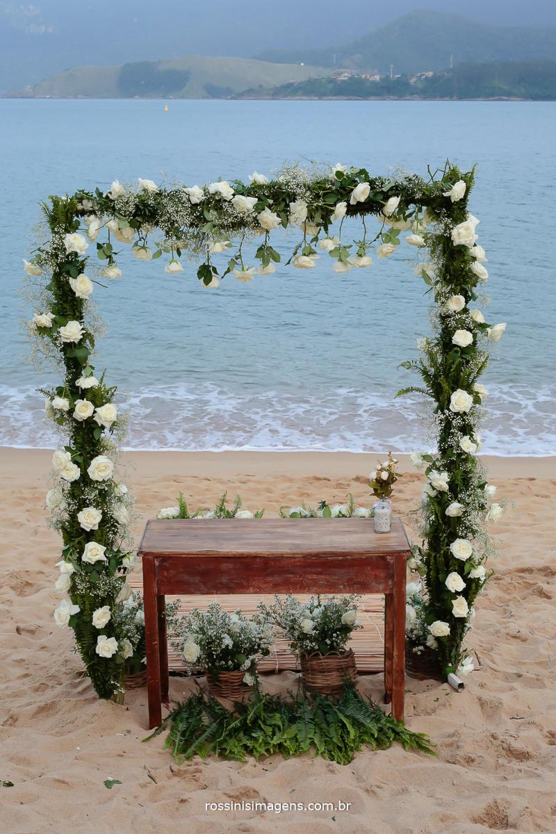 Pergolado com flores, na praia para a cerimonia de casamento civil de Thais e Alexandre