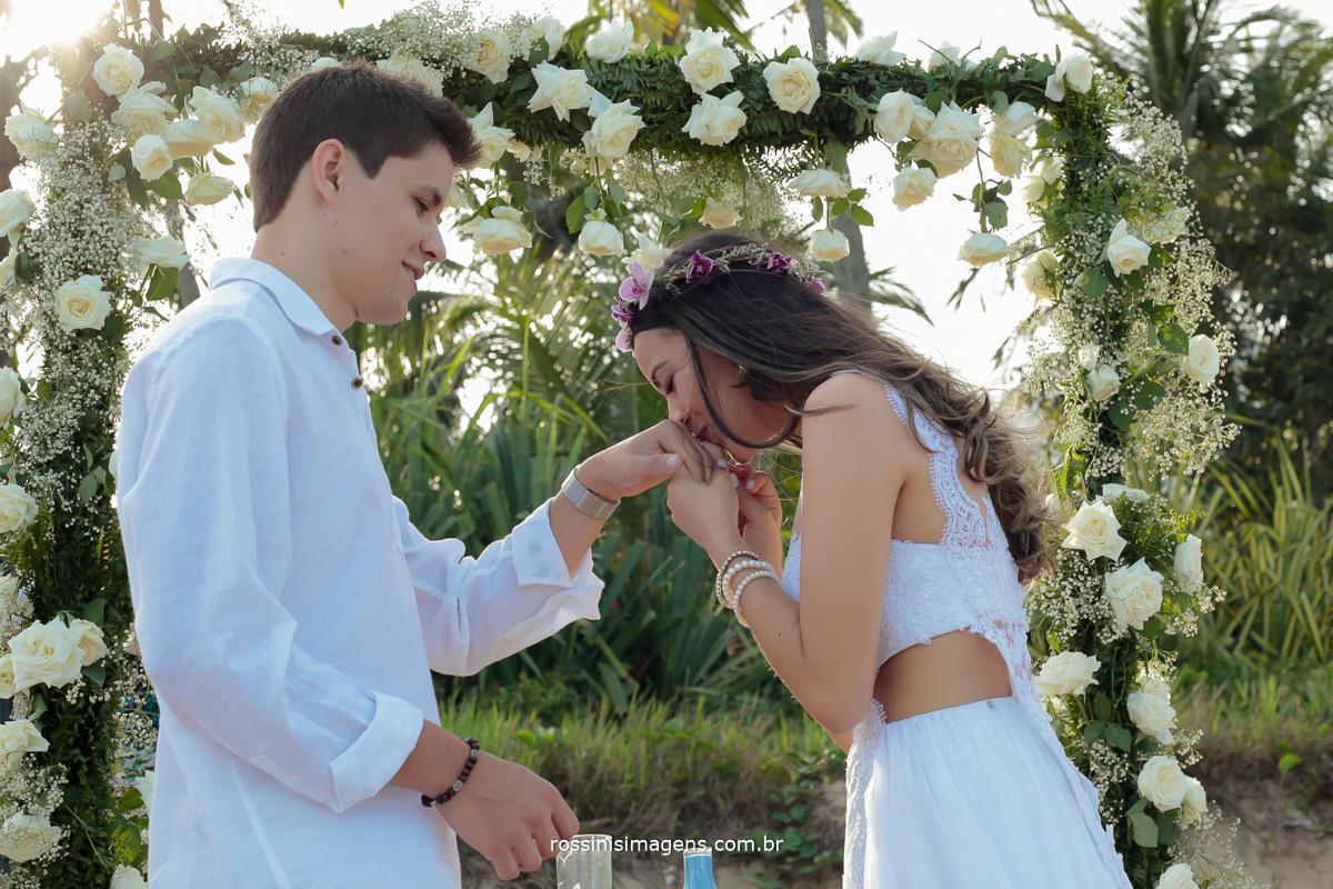 noiva colocando a aliança em seu esposo, casamento na praia repleto de detalhes produzidos pela noiva e seus familiares, muito amor e carinho para realização desse lindo dia