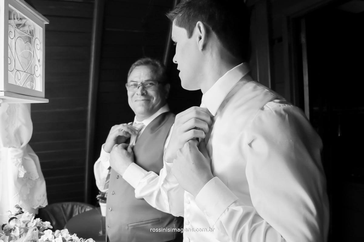 fotografia de making of do noivo colocando a gravata ao lado de seu pai que esta lhe ajudando com todos os detalhes para se arrumar, presença muito importante do pai para participar dos momentos que antecedem o casamento
