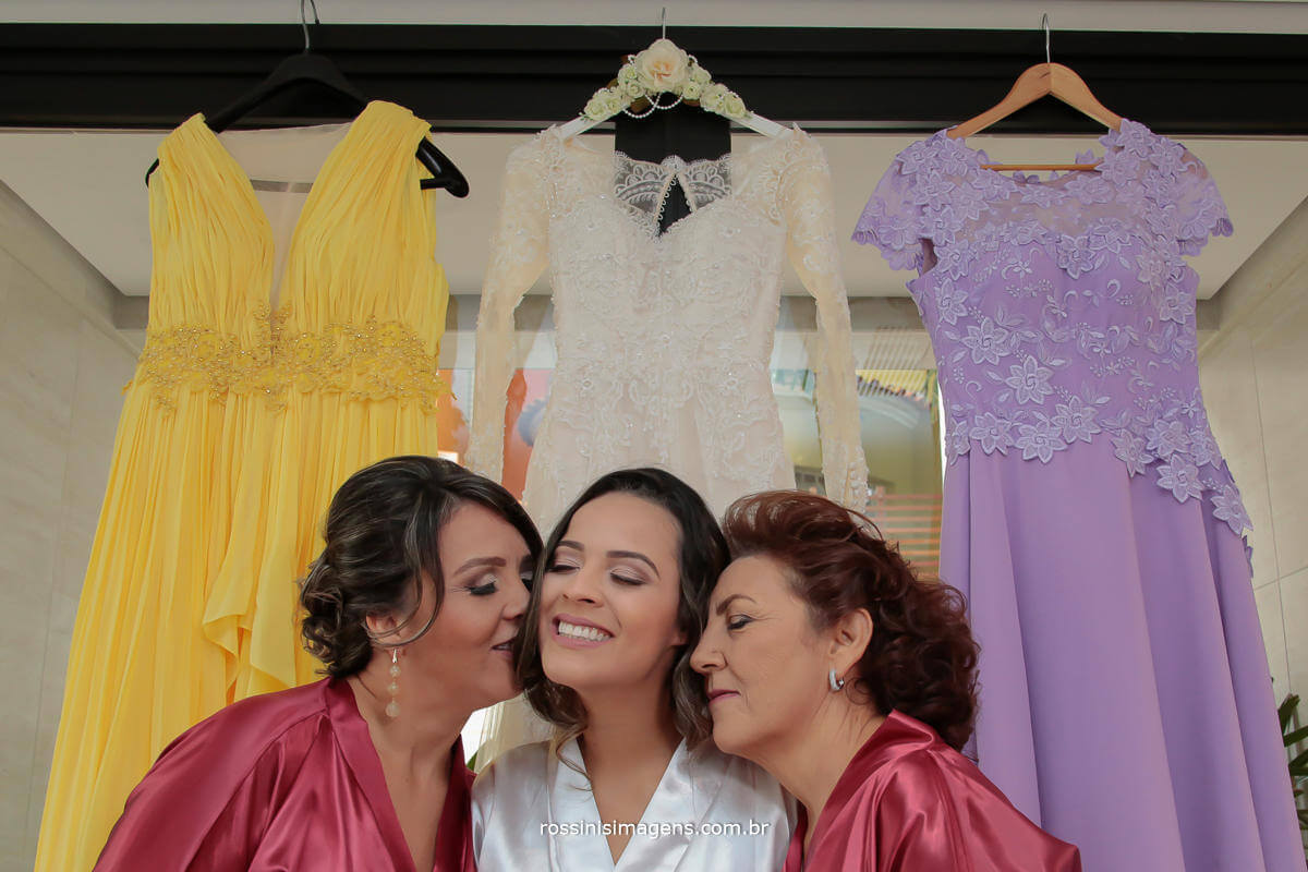 fotografia de casamento mae da noiva, noiva e sogra, juntas no making of da noiva com os vestidos ao fundo, momentos antes da cerimonia de casamento