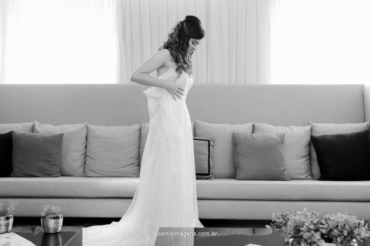 noiva colocando vestido de noiva sozinha, noiva segurando o vestido no corpo, momento decisivo na preparação do casamento o vestido de noiva, esse foi escolhido a dedo e é maravilhoso de tão lindo e cheio de detalhes