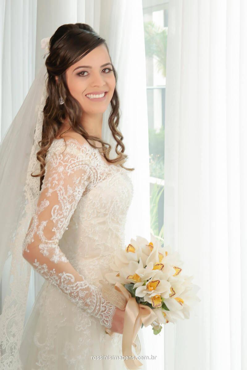 foto de noiva pronta em frente a janela, exibindo seu lindo e maravilhoso vestido cheio de detalhes, um bordado e o buquê e o crucifixo, Rossinis Imagens - Fotografia e Video de Casamento