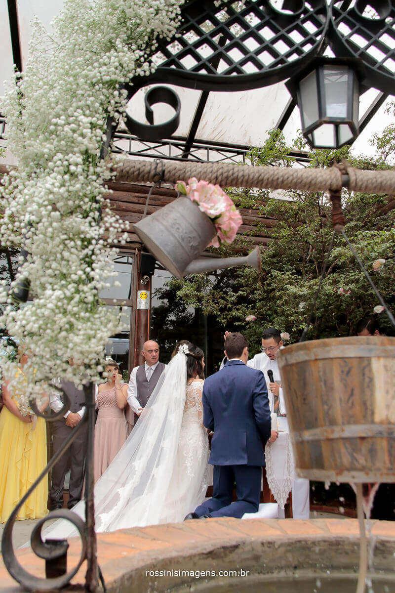 fotografia de casamento durante o cerimonial noivos de costa, mostrando os padrinhos