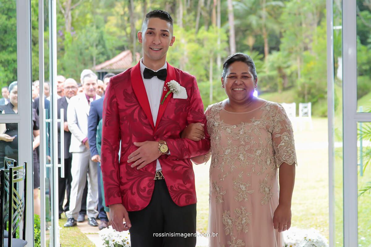 entrada do noivo de terno vermelho com sua mãe